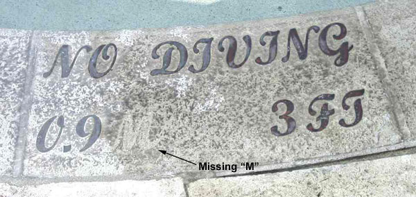 Missing M from concrete installed bronze letters